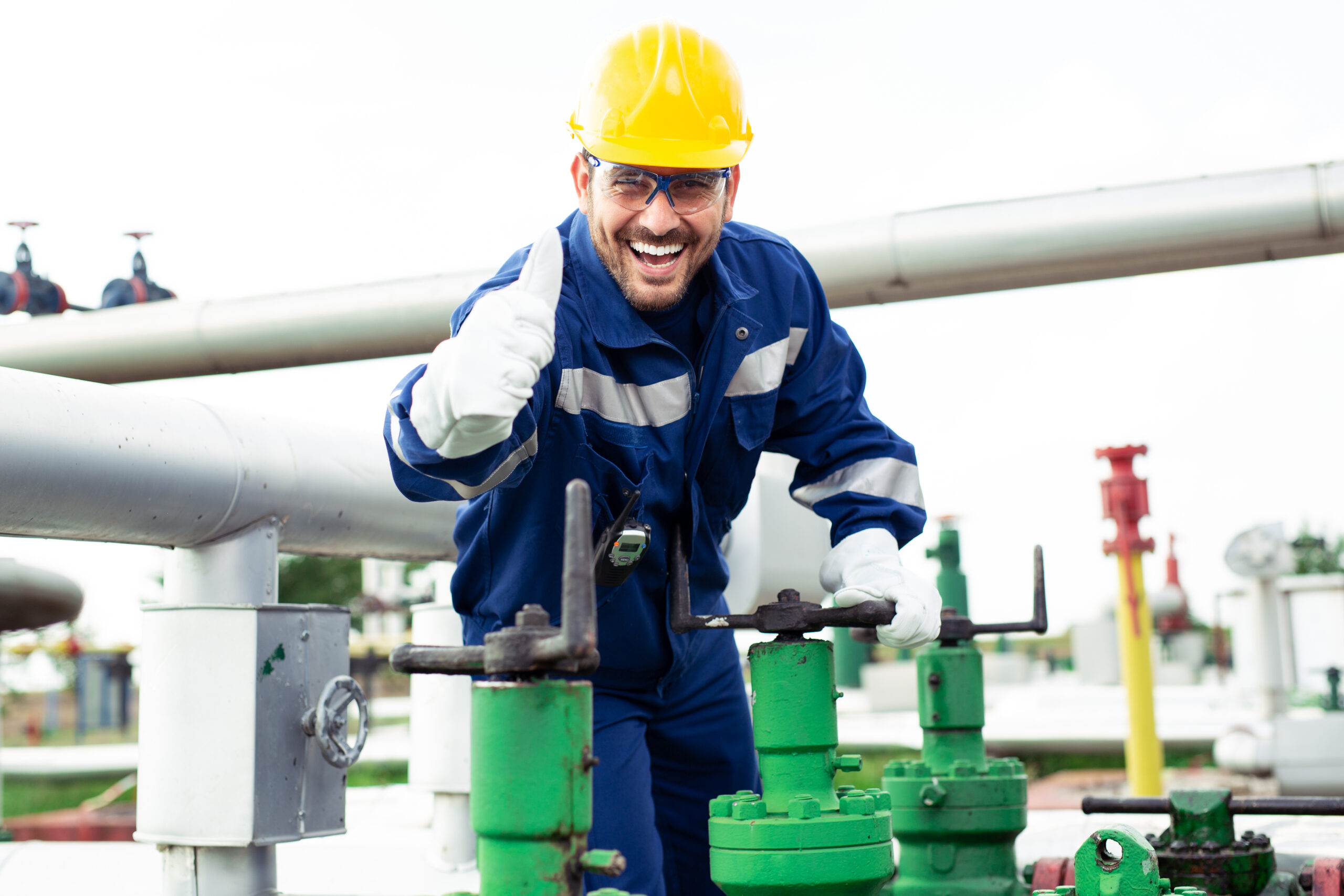 Worker closes the valve on the oil pipeline